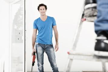 Deutschland, Köln, Junger Mann mit Bohrmaschine , Wohnungsrenovierung