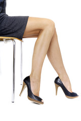 Junge Frau in Mini-Kleid sitzt auf dem Stuhl