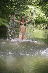 Teenager-Mädchen, Mädchen spritzt Wasser im Fluss