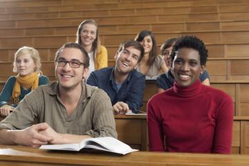 Deutschland, Leipzig, Studenten sitzen im Hörsaal und lächeln