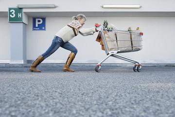 Deutschland, Junge Frau treibt Warenkorb