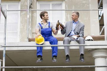Architekt und Bauarbeiter vor Ort, trinken Bier