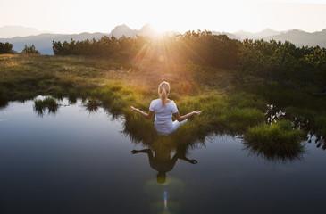 Österreich, Salzburger Land, junge Frau sitzt am Bergsee, Meditation