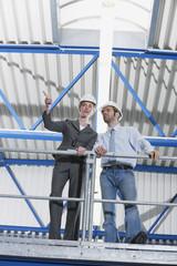 Deutschland, Neukirch, Mann und Architektin stehen in Industriehalle