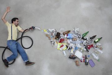 Mann sprüht Müll aus einem Tankstutzen
