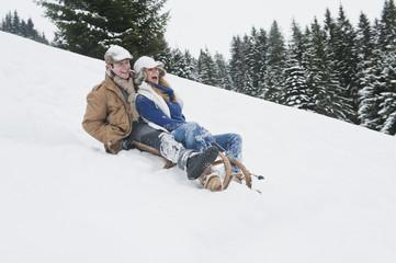 Österreich, Land Salzburg, Flachau, Junger Mann und Frau Rodeln im Schnee