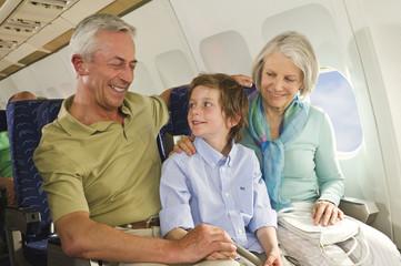 Deutschland, München, Bayern, Junge sitzt neben älteren Menschen in der Economy-Klasse Verkehrsflugzeug