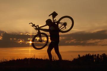 Deutschland, Niederbayern, Biker tragen Fahrrad bei Sonnenuntergang