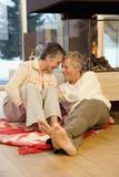 Älteres Ehepaar sitzt vor dem Kamin
