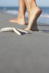 Italien, Sardinien, Füße der Frau zu Fuß am Sandstrand