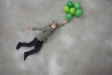 Junge mit Ballons auf grauem Hintergrund