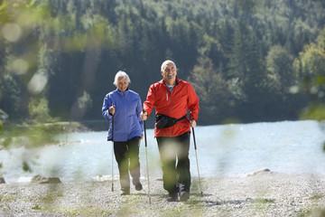 Deutschland, Bayern, Walchensee, älteres Paar, Nordic Walking am Seeufer