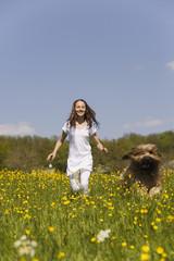 Deutschland, Baden Württemberg, Tübingen, Mädchen mit Hund läuft durch Wiese