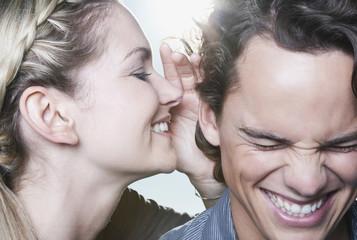 Italien, Toskana, Junge Frau flüstert in Ohr des Mannes, close up