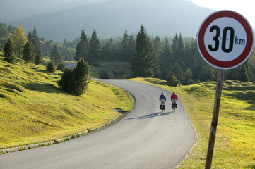 Deutschland, Bayern, Mittenwald, Paar Mountainbiken, Verkehrszeichen im Vordergrund