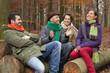 Deutschland, Berlin, Wandlitz, Männer und Frauen sitzen auf Baumstamm