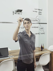 Deutschland, Köln, Junge Frau schreibt auf Glas, Fenster