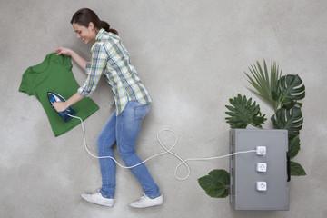 Frau bügelt T-Shirt, Bügeleisen durch Stromkabel mit einer Pflanzenkiste verbunden