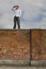 Deutschland, Bayern, München, Junger Mann auf Mauer und beobachtete aus