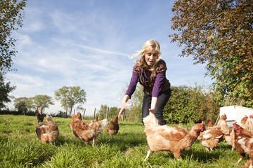 Deutschland, Sachsen, Junge Frau fängt Hühner auf dem Bauernhof