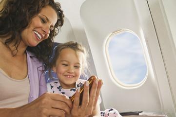 Deutschland, München, Bayern, Frau und Mädchen mit Handy in der Economy-Klasse Verkehrsflugzeug