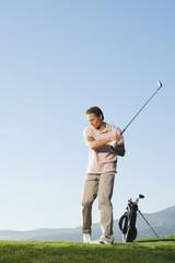 Italien, Kastelruth, Mann mittleren Alters spielt Golf auf dem Golfplatz