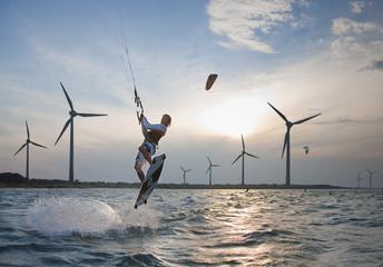 Kroatien, Zadar, Kitesurfer springend vor Windkraftanlage