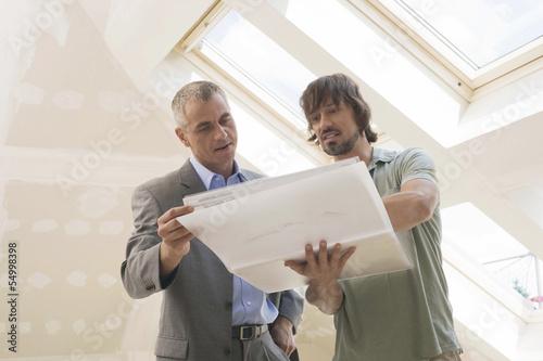 Zwei Männer schauen auf Bauplan