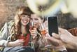 Deutschland, Berlin, Junge Frauen mit Champagner-Glas und ein Mann, machen Fotos