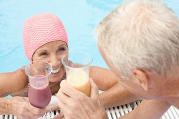 Deutschland, älteres Paar trinkt Cocktails am Pool
