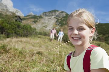 Österreich, Salzburg Land, Filzmoos, Mädchen mit den Eltern im Hintergrund