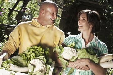 Österreich, Salzburg, Flachau, Paar hält Gemüse im Garten
