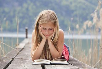 Österreich, Teenager-Mädchen liest ein Buch auf einem Steg