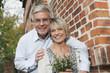Deutschland, Kratzeburg, älteres Paar, Senioren mit Blumenstrauß am Landhaus, Lächeln