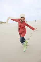 Deutschland, St. Peter-Ording, Nordsee, Frau, Spaß in den Sanddünen, Lächelnd