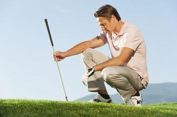 Italien, Kastelruth, Mann mit Golfschläger auf Golfplatz