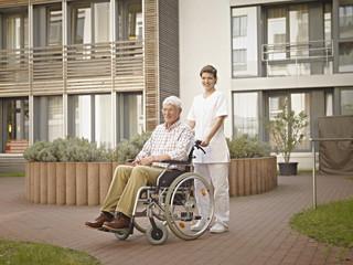 Deutschland, Köln, Hausmeister schiebt Senior, Rentner im Rollstuhl außerhalb Pflegeheim