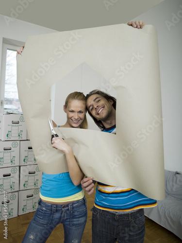 Paar schaut durch Loch im Papier