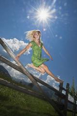 Österreich, Salzburger Land, Junge Frau springt über Zaun
