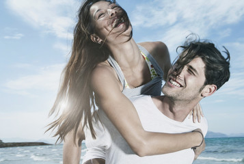 Spanien, Mallorca, Junger Mann trägt Frau auf dem Rücken am Strand
