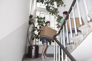 Deutschland, Köln, Junges Paar Umzugskarton auf der Treppe , Wohnungsrenovierung