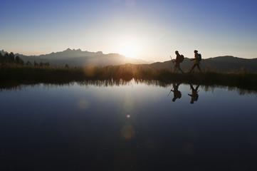 Österreich, Salzburg, Paar zu Fuß in der Nähe von Bergsee bei Sonnenaufgang
