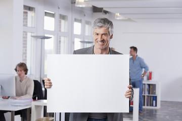 Deutschland, Bayern, München, Erwachsene halten Plakat im Büro