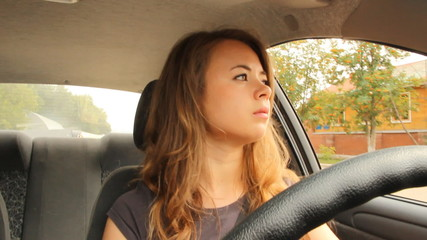 The young girl behind the wheel of a car