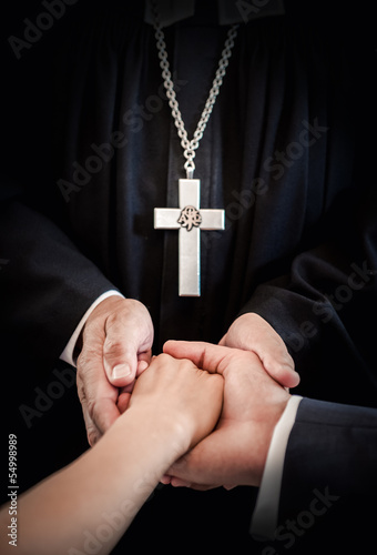 Priest holding bride's and groom's hands during wedding ceremony