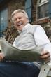 Deutschland, Kratzeburg, erwachsener Mann liest Zeitung