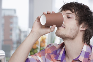 Deutschland, Köln, Junger Mann trinkt Kaffee