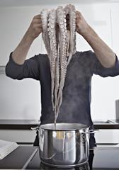 Deutschland, Köln, Mann in der Küche kochen Krake