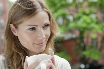 Deutschland, Frau hält Tasse Kaffee