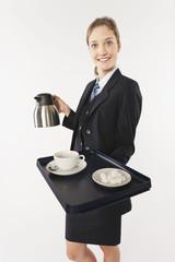 Junge Stewardess mit Serviertablett und Heißgetränk vor weißem Hintergrund